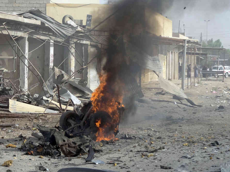Smoke rises from the wreckage of a vehicle in Kirkuk, Iraq. A bomb in it exploded — one of a seri