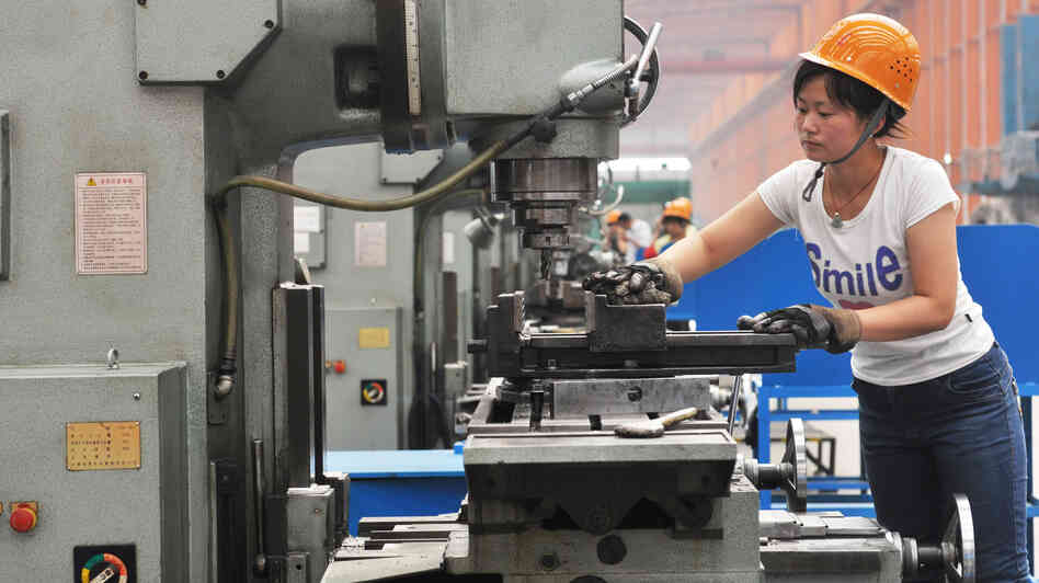 A Chinese worker operates a machine at a factory in Binzhou in northeast China's Shandong