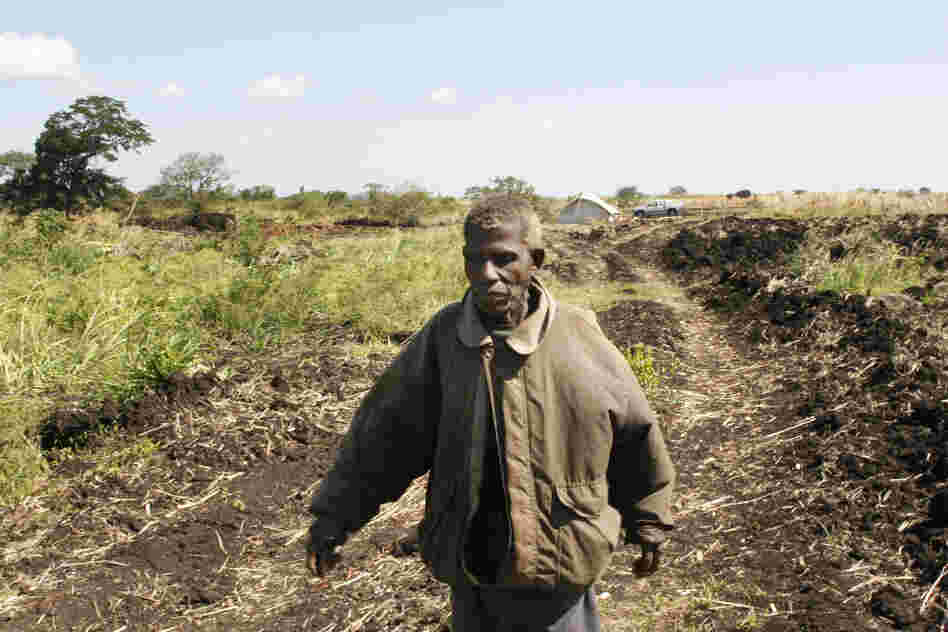 Vitorino Munalile walks past a field where he used to grow crops. Workers at the investor-owned farm recently plowed up the land for the farm's own use.