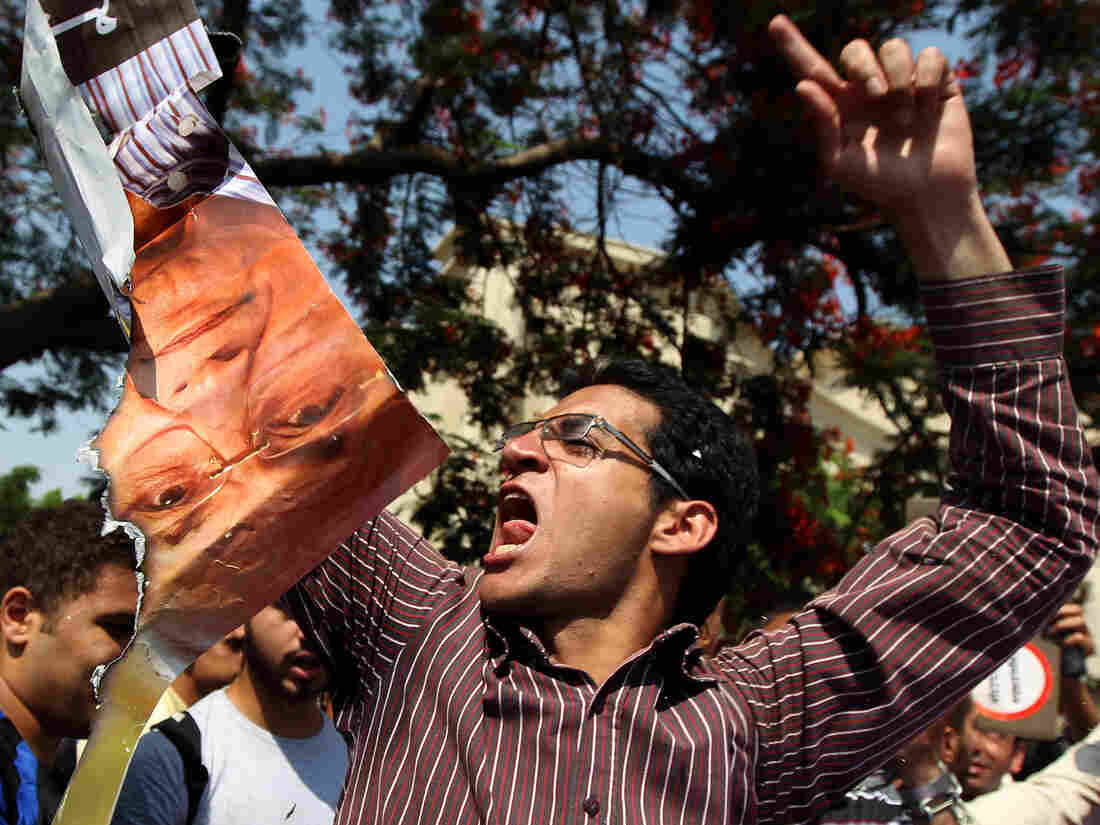 An Egyptian protester chants slogans as he holds a ripped poster of presidential candidate Ahmed Shafiq outside the Supreme Constitutional Court in Cairo today.