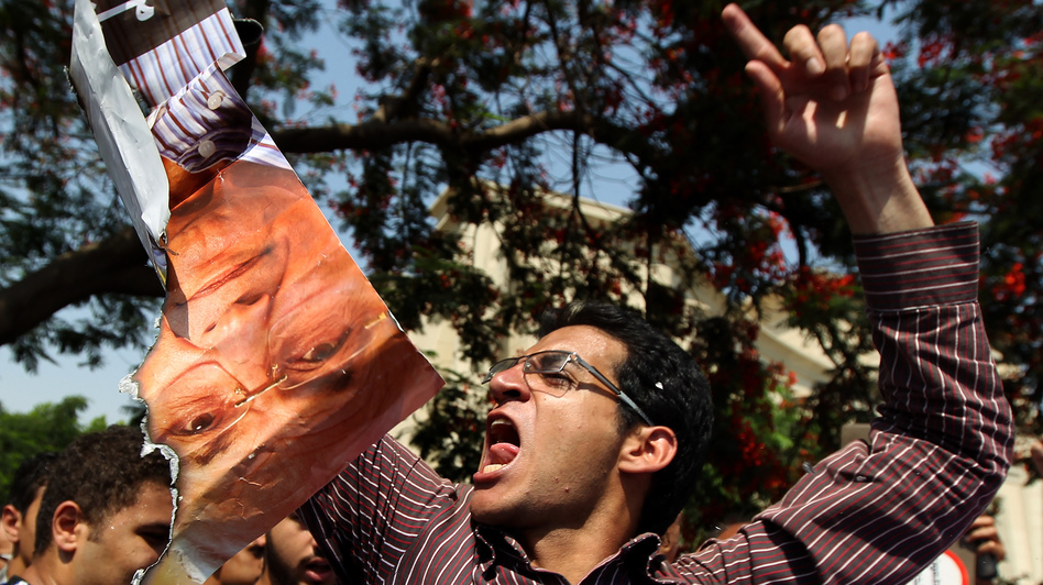 An Egyptian protester chants slogans as he holds a ripped poster of presidential candidate Ahmed Shafiq outside the Supreme Constitutional Court in Cairo today. (AFP/Getty Images)