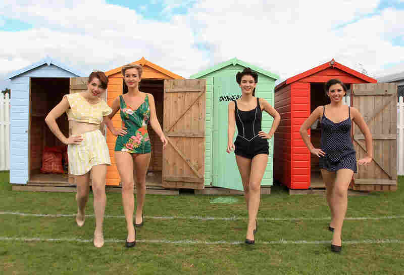 Women in vintage bikinis pose in the drivers' enclosure during Goodwood Revival 2010 in Chichester, England. The event was based around a classic car race meeting and air show but celebrated all things 1945-1966.
