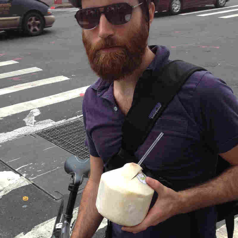John Gordon Gauld, a 35-year old artist, bikes with coconut water in New York City.
