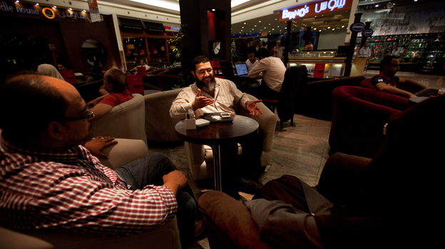 Mohammed Tolba (center) talks with friends at a coffee shop in the Cairo suburbs. The 33-year-old Egyptian is trying to change the public perception of Salafists, Muslims who believe in a literal interpretation of the Quran. (NPR)