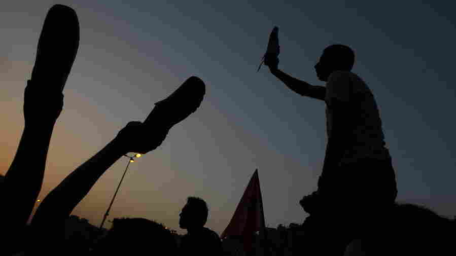 Egyptian anti-military protesters waved their shoes — a way of showing their extreme anger — as they demonstrated in Cairo's Tahrir Square on Thursday. More protests are planned for today.