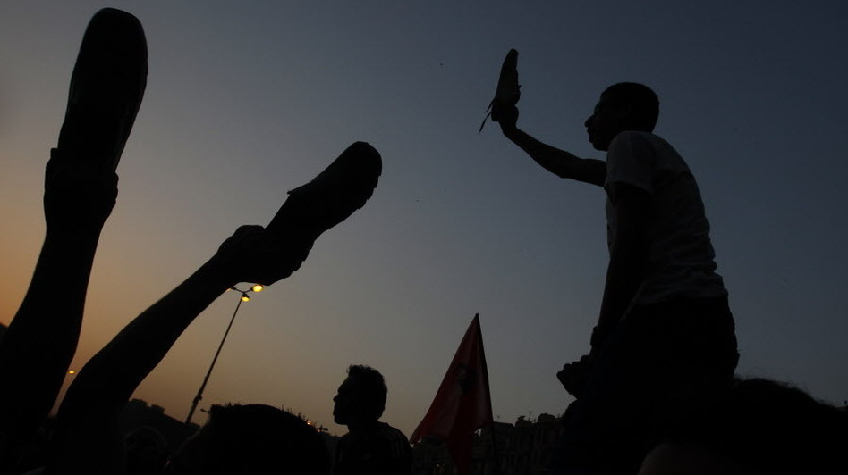 Egyptian anti-military protesters waved their shoes — a way of showing their extreme anger — as they demonstrated in Cairo's Tahrir Square on Thursday. More protests are planned for today. (AFP/Getty Images)