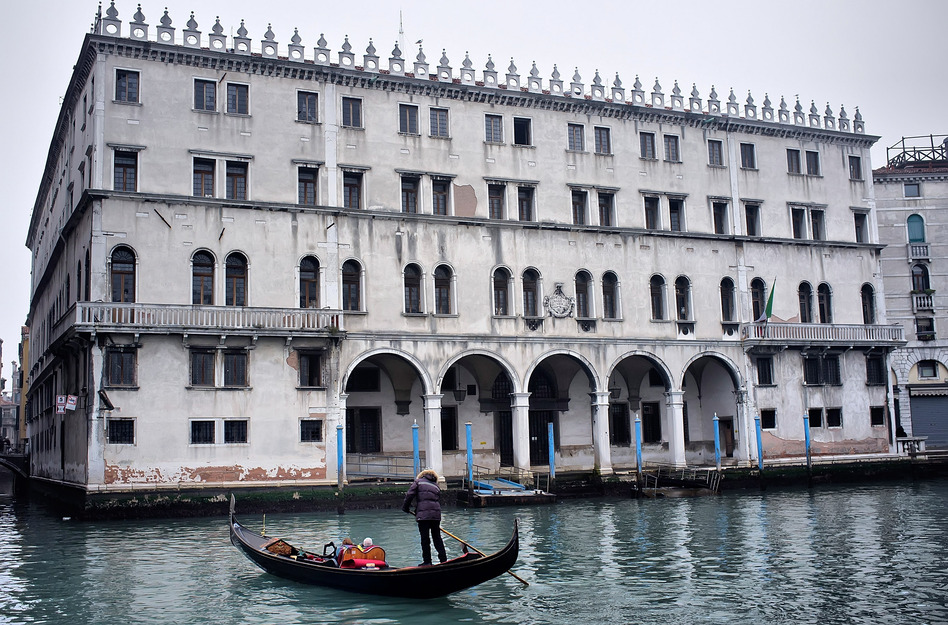 A gondola sails in front of the Fondaco dei Tedeschi, which has been sold to Benetton Group. The clothing company plans to convert the Venice landmark into a shopping mall.