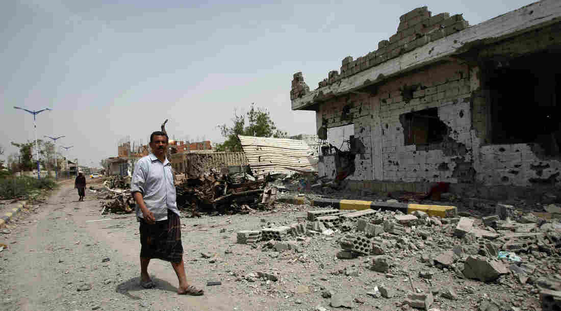 Yemeni residents walk past vehicles and houses which were destroyed during recent fighting between the army and militants on a road leading to the city of Zinjibar on Thursday.