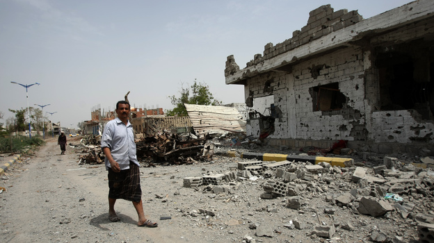 Yemeni residents walk past vehicles and houses which were destroyed during recent fighting between the army and militants on a road leading to the city of Zinjibar on Thursday. (AFP/Getty Images)
