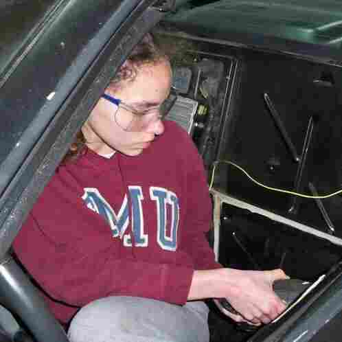 14-year-old Kathryn DiMaria drilling door rivets in her Pontiac Fiero.
