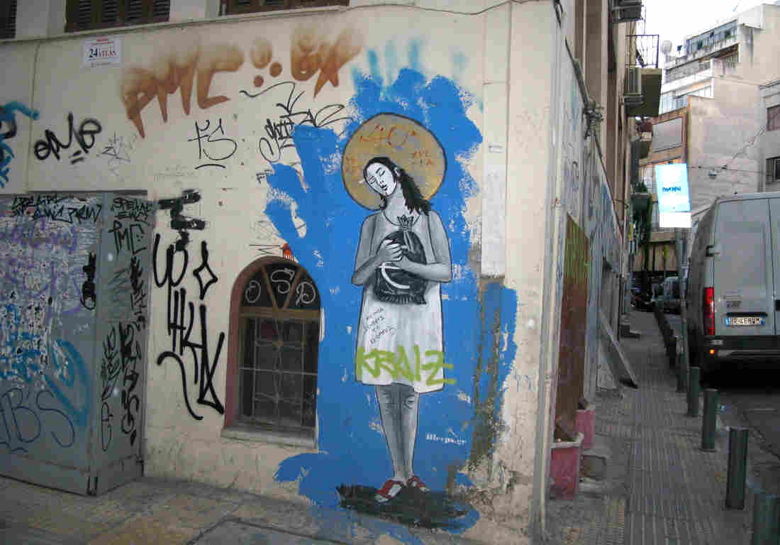 "Graffiti in the rundown Athens neighborhood of Psiri depicts a woman clutching a sack of euros, a golden halo on her head and the title, ""40 Years of Debt-ocracy."" The street artist goes by the tag Bleeps.gr."