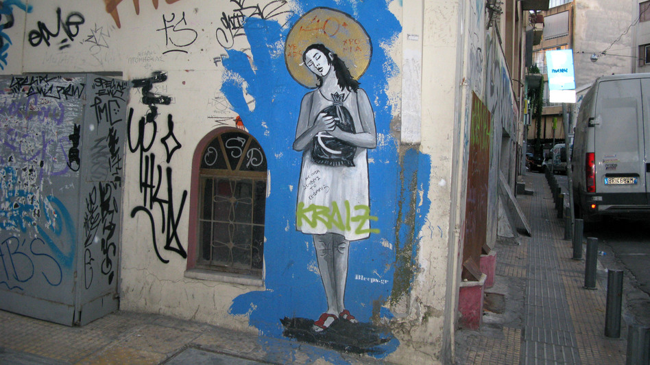 "Graffiti in the rundown Athens neighborhood of Psiri depicts a woman clutching a sack of euros, a golden halo on her head and the title, ""40 Years of Debt-ocracy."" The street artist goes by the tag Bleeps.gr. (NPR)"
