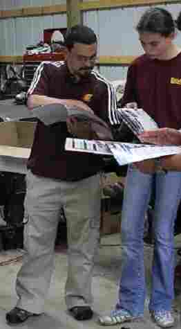 Jerry DiMaria and his daughter, Kathryn, look through Pontiac Fiero catalogs.