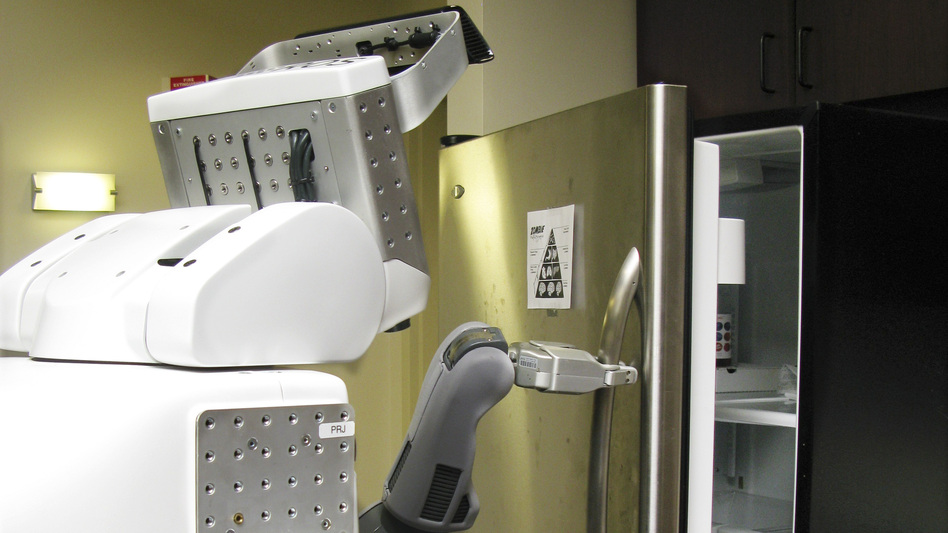 A PR2 robot named Jake opens a refrigerator at Willow Garage's office.