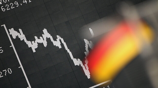Frankfurt: A German flag hung today in front of a board displaying the DAX stock index.