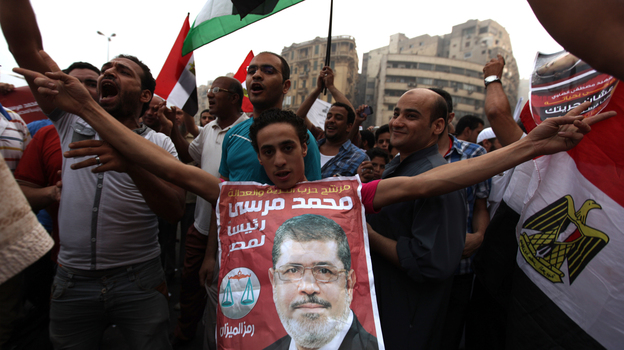 Supporters of Muslim Brotherhood candidate Mohammed Mursi (in portrait) celebrated today in Cairo's Tahrir Square. (AFP/Getty Images)
