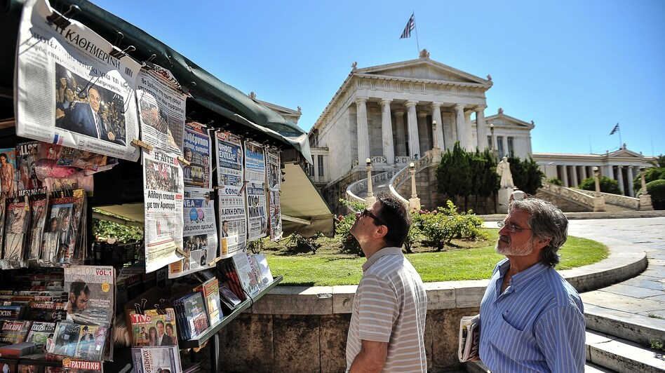 Two men read newspaper headlines in Athens on Monday as conservative Greek lawmakers raced to form a government a day after parliamentary elections. (AFP/Getty Images)