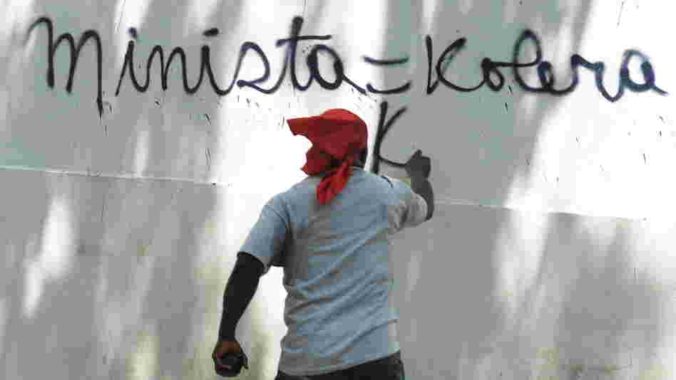 A Haitian protester in Port-au-Prince last year spray-paints a wall, equating the UN mission in Haiti (abbreviated here as MINISTA) with cholera.