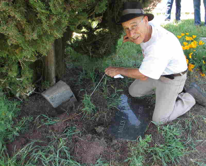 """Tony Pires uses a metal rod to find a grave marker. Decades of growing plants, pecking birds and digging gophers can make things strangely """"disappear"""" in old cemeteries like Gilliam."""