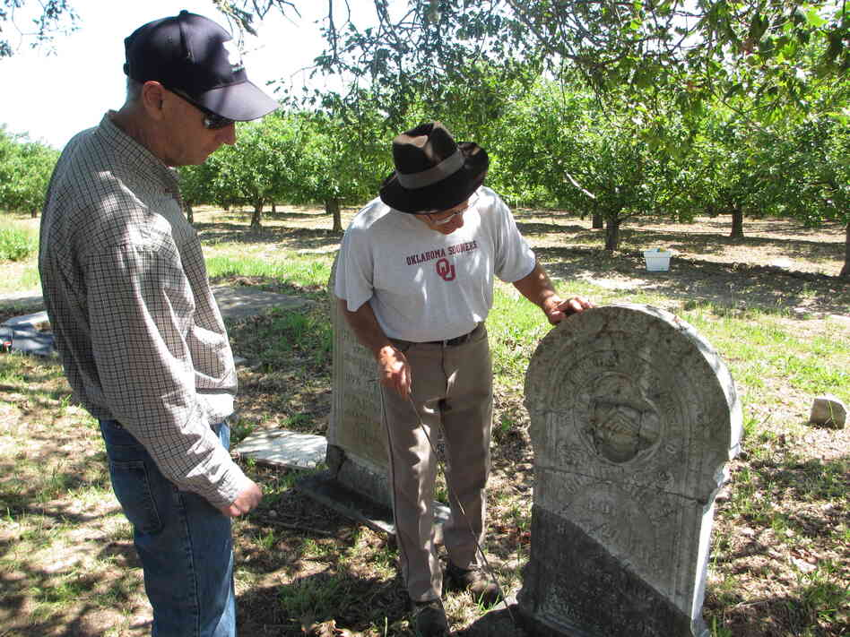 Tony Pires (right) inspects a repaired headstone for Mitchell Gilliam (Polly's father) with Jack Boatwright of the U.S. Geological Survey.