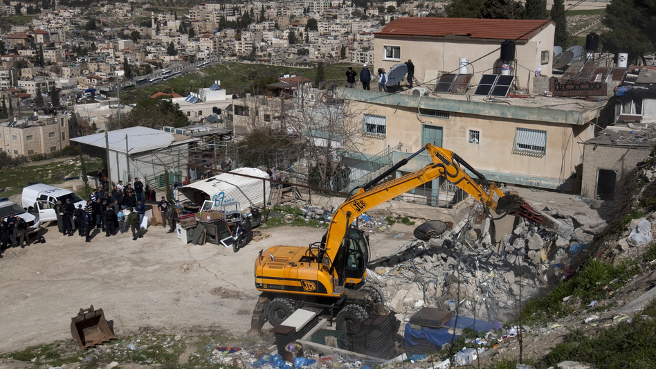 Israeli soldiers keep watch as a bulldozer demolishes a house belonging to a Palestinian resident in east Jerusalem on Feb. 13. Israel said the home was built without a permit. (AFP/Getty Images)