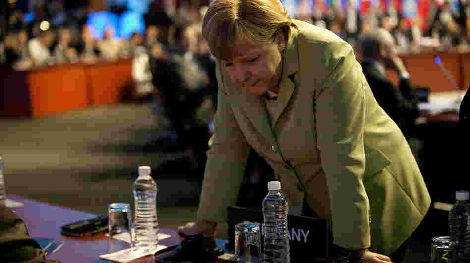 German Chancellor Angela Merkel speaks with members of her delegation before the first plenary session of the G-20 Leaders' Summit in Los Cabos, Mexico, on Monday.