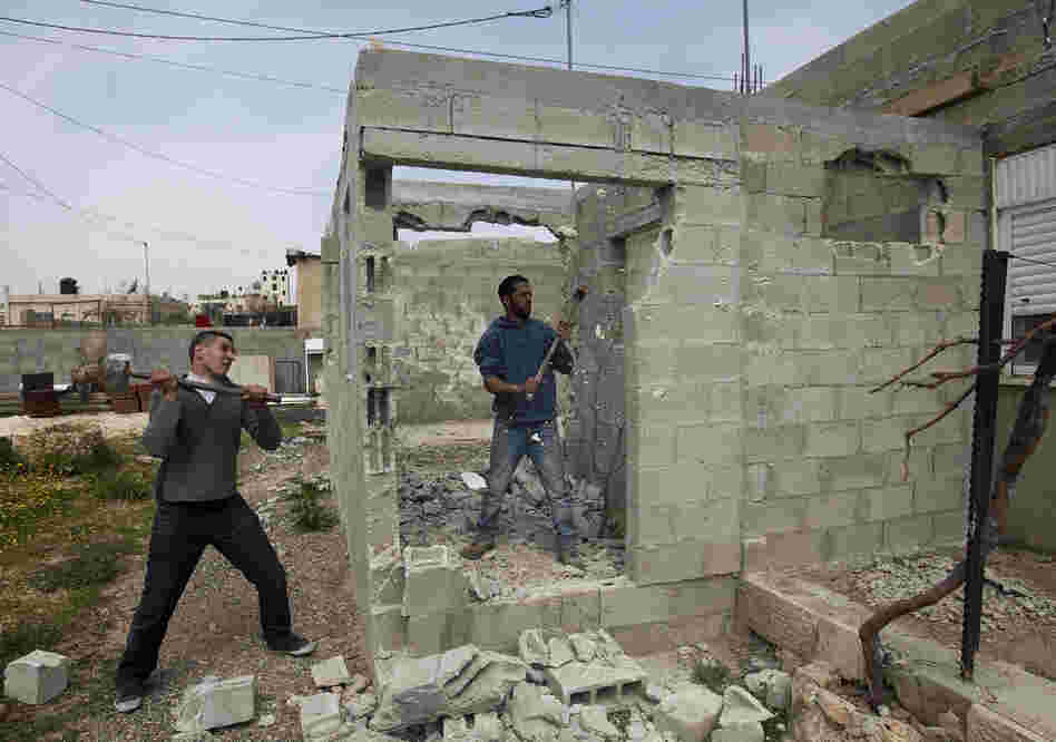 Palestinian Motasem Farrah (center) and a friend tear down Farrah's home in an Arab neighborhood in east Jerusalem, March 12. Israel often tells Palestinians who build without permits that they must tear down the house themselves or they will be charged by Israel for the cost of knocking it down.