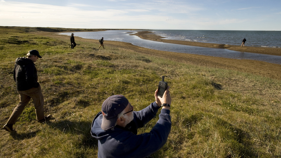 Richard E. Reanier, an independent archaeologist working for Shell Oil, uses GPS to record the location of the remains of a sod house along the Chukchi Sea coast near Wainwright, Alaska, in July 2011. (Getty Images)