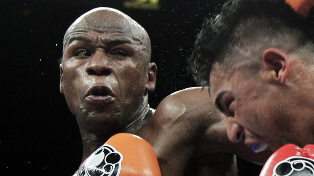 Floyd Mayweather Jr., left, punching Victor Ortiz during t