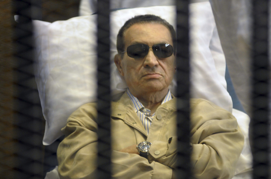 Egypt's ex-President Hosni Mubarak lays on a gurney inside a barred cage in the police academy courthouse in Cairo, Egypt during his sentencing in June.