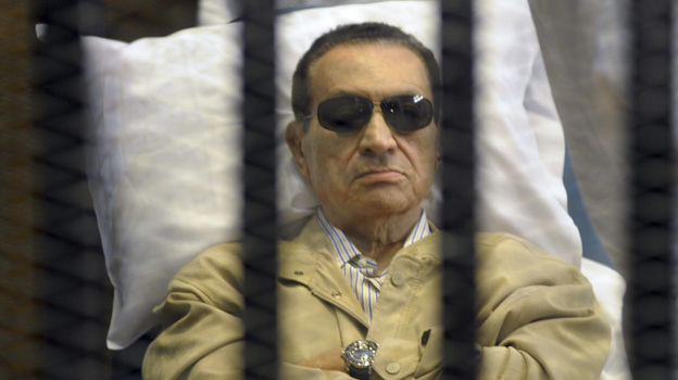 Egypt's ex-President Hosni Mubarak lays on a gurney inside a barred cage in the police academy courthouse in Cairo, Egypt during his sentencing in June. (AP)
