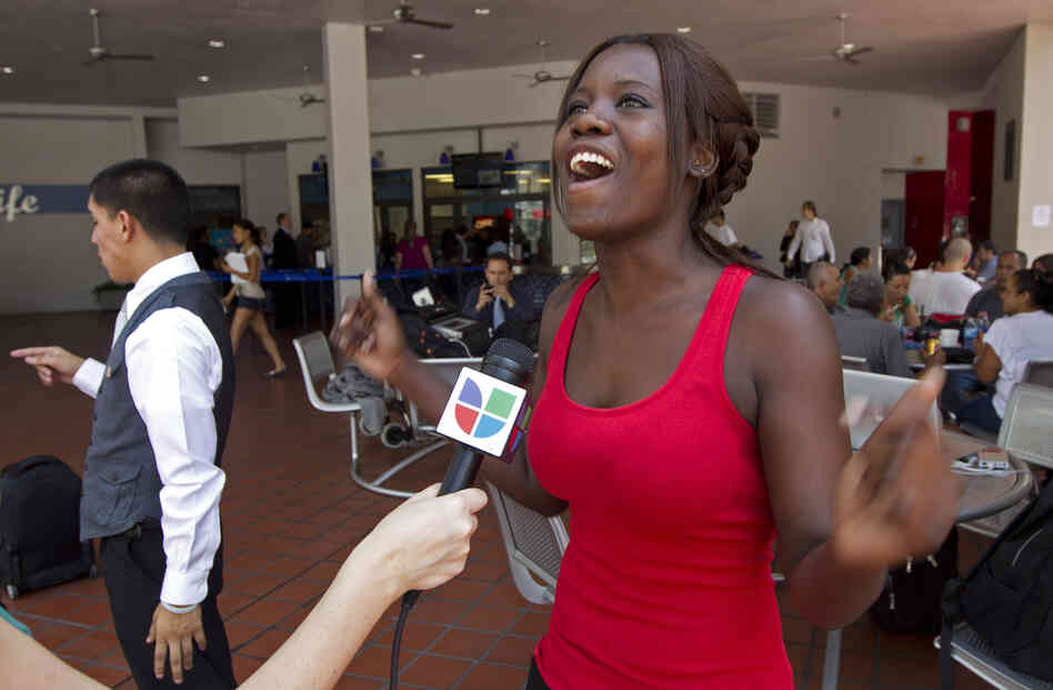 Niouseline St. Jean, originally from Turks and Caicos Islands who lives in the U.S. illegally, reacts as she talks to the media abou