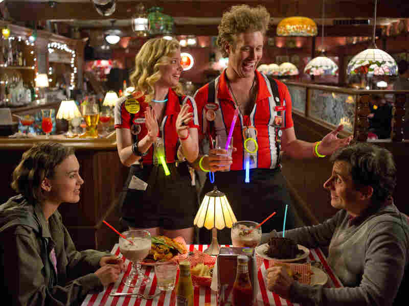 Once Dodge and Penny hit the road, the movie features a series of episodic encounters, including one with Katie (Gillian Jacobs, center left) and Darcy (T.J. Miller) at a T.G.I. Friday's-style eatery.