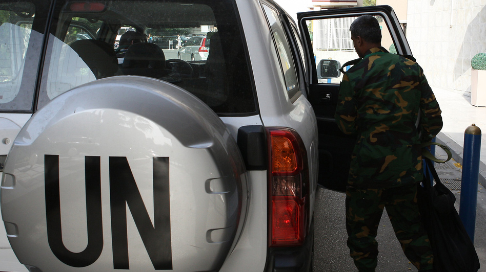 The United Nations observer team in Syria suspended its mission last Saturday, June 16, after facing repeated dangers and difficulties in trying to do its work. One observer is shown here next to a U.N. vehicle outside a hotel in Damascus. (AFP/Getty Images)