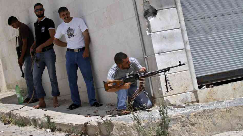 A Syrian rebel fires his weapon during clashes with Syrian troops near Idlib, in northern Syria, on June 15. The conflict has gone on for well over a year, but the international community has shown no appetite for a military intervention.
