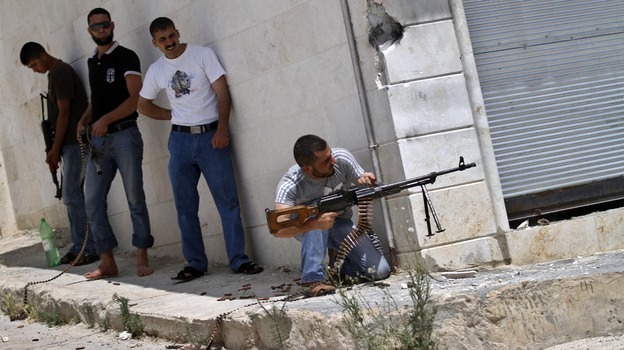 A Syrian rebel fires his weapon during clashes with Syrian troops near Idlib, in northern Syria, on June 15. The conflict has gone on for well over a year, but the international community has shown no appetite for a military intervention. (AP)