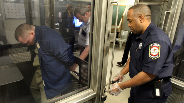 Lt. Robert DuBois (center) handcuffs Tamms Correctional Center inmate Damien Terry (left) before he is taken from his holding cell in 2009. State budget constraints are forcing the facility — Illinois' only supermaximum security prison — to either close or be converted to a lower-security prison. (MCT/Landov)