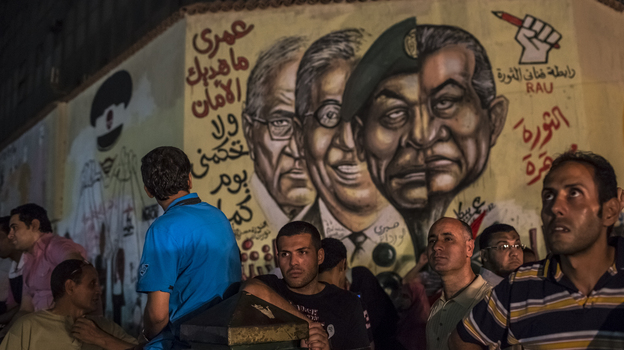 In Cairo's Tahrir Square on Tuesday night, men gathered in front of graffiti showing ousted President Hosni Mubarak and others from his regime. (Getty Images)
