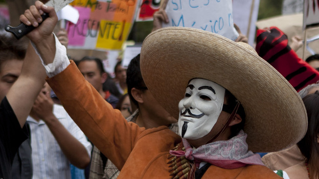 A man wearing a mask holds up a machete during a protest in May against a possible return of the old ruling Institutional Revolutionary Party in Mexico City. (AP)