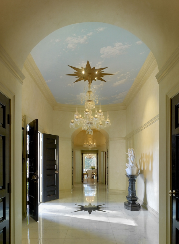 Williams thought a home's entrance should make a statement. In this Colonial Revival residence, designed in Beverly Hills for the Landis family in 1955, the narrow foyer has large double doors that swing open to reveal a high ceiling covered in a trompe l'oeil sky, and a lavish chandelier hung from a starburst medallion. The medallion's design is repeated on the marble floor.