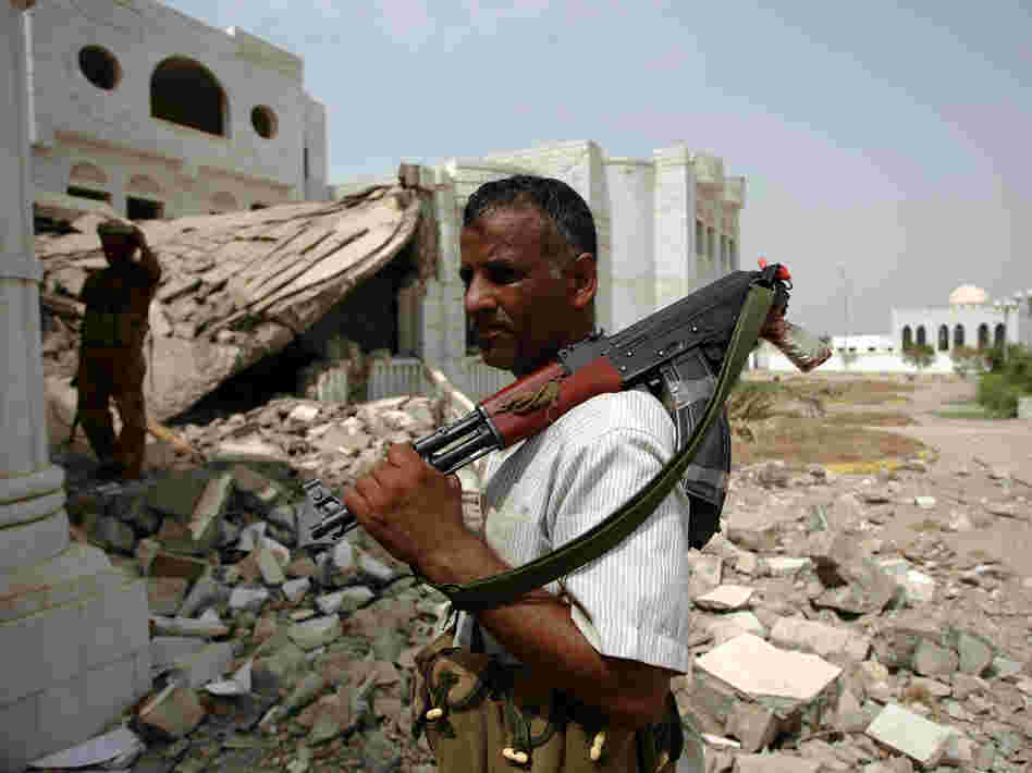 An armed Yemeni tribesman loyal to the army stands near a destroyed government building in the provincial capital of Zinjibar last week. The Yemeni military drove al-Qaida militants out of the city two days earlier.