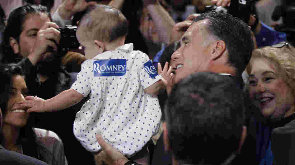 Republican presidential candidate Mitt Romney gives a young supporter a boost at the National Association of Latino Elected and Appointed Officials conference in Orlando, Fla., on Thursday.