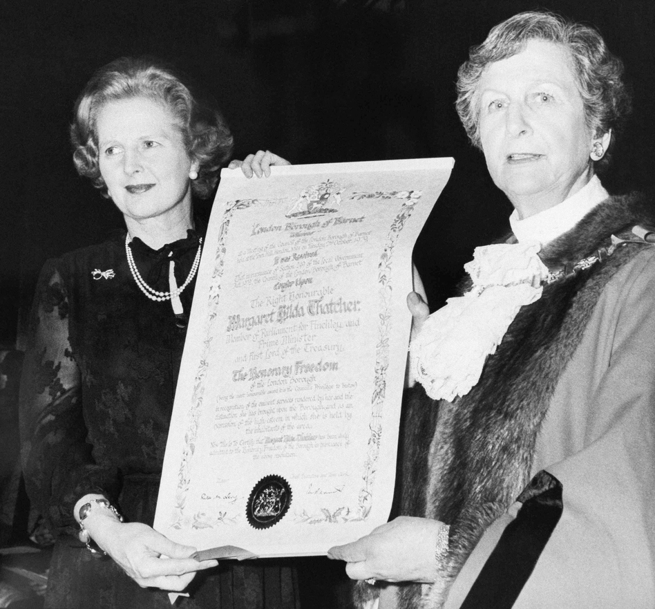 Prime Minister Thatcher (left) shows off her scroll after receiving an honor from the London Borough of Barnet at Barnet Town Hall, Feb. 6, 1980. With Thatcher is the mayor of Barnet, Councilor Rita Levy. (AP)