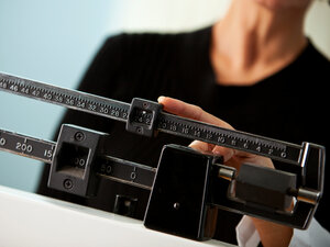A woman checks her weight at the doctor's office.