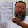 In a park in Beijing, Chinese artist Ai Weiwei holds a copy of a government document informing him of the expiry of his bail term.