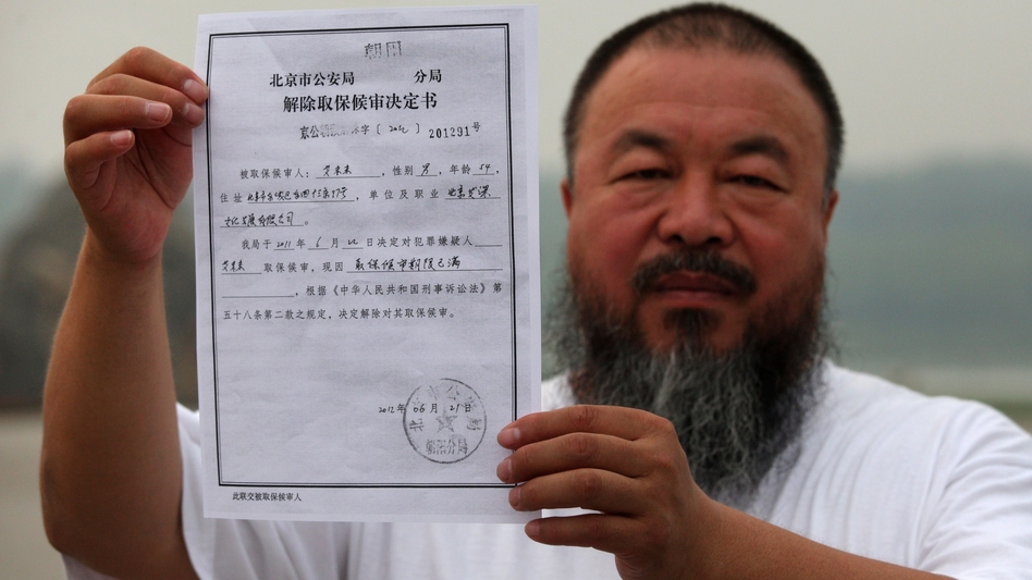 In a park in Beijing, Chinese artist Ai Weiwei holds a copy of a government document informing him of the expiry of his bail term. (AFP/Getty Images)