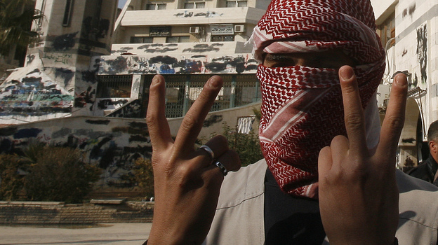 A Syrian youth flashes the victory sign as he stands in front of a building that was covered with anti-government graffiti — though local authorities painted over it — in the town of Duma, outside Damascus, in February. (AFP/Getty Images)