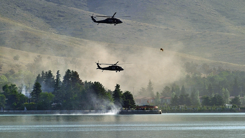 Responding to a Taliban attack, NATO Black Hawk helicopters fly over the Spozhmai Hotel on Lake Qargha outside Kabul. More than 20 people were killed before the Taliban fighters were shot dead. (AFP/Getty Images)