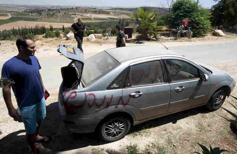 "Vandals slashed car tires and spray-painted graffiti in the village of Neve Shalom earlier this month. Here, Jewish Israeli and Arab Israeli men inspect a car that was spray-painted with the word ""Revenge."""