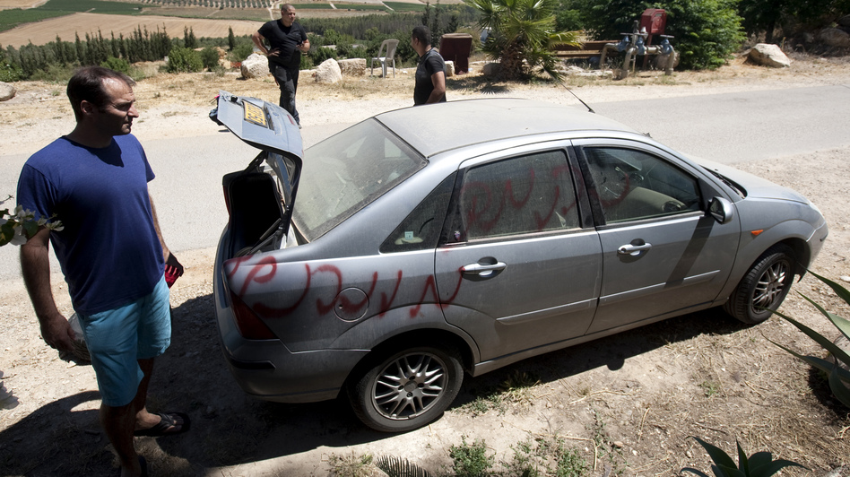 """Vandals slashed car tires and spray-painted graffiti in the village of Neve Shalom earlier this month. Here, Jewish Israeli and Arab Israeli men inspect a car that was spray-painted with the word """"Revenge."""""""